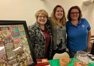 Three volunteers sell raffle tickets at Brevillier Village event.