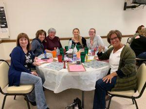 Six women sitting around the table at Brevillier Village bingo event.