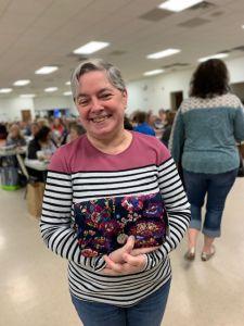 Woman holding handbag that she won at Brevillier Village handbag bingo event.