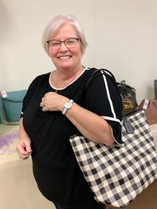Woman holding handbag that she won at Brevillier Village handbag bingo event.