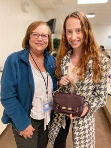Women holding handbag that she won at Brevillier Village handbag bingo event.