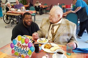 Visitor eats breakfast with Brevillier Village resident.