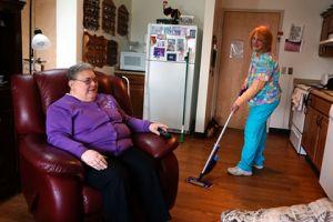 Brevillier Village volunteer vacuums Barnabas Court residents floor.