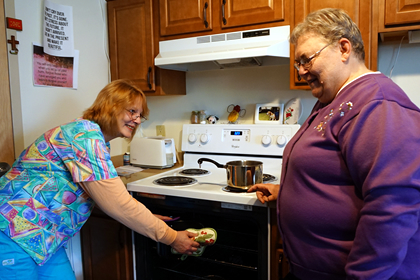 Brevillier Volunteer helps Barnabas Court resident cook dinner.