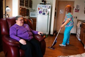 Brevillier Village volunteer vacuums Barnabas Court residents floor.