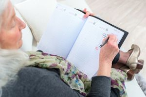 Women writes in her schedule book.